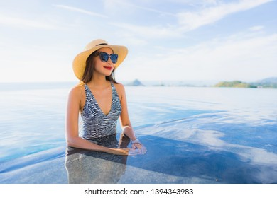 Portrait beautiful young asian woman smile happy relax around swimming pool in hotel resort for leisure travel and vacation concept