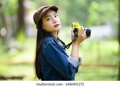 Portrait of beautiful young Asian woman with camera at summer green park