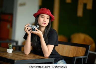 Portrait of beautiful young Asian woman with  retro camera in coffee shop