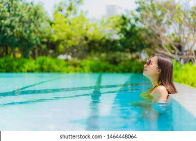 Portrait beautiful young asian woman smile happy relax and leisure in the swimming pool hotel resort for travel and vacation concept