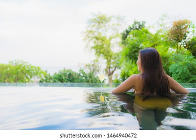 Portrait beautiful young asian woman with champagne glass for relax leisure in swimming pool at hotel resort for holiday vacation concept
