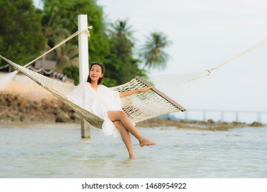 Portrait beautiful young asian woman sitting on hammock around sea beach ocean for relax in holiday vacation travel concept