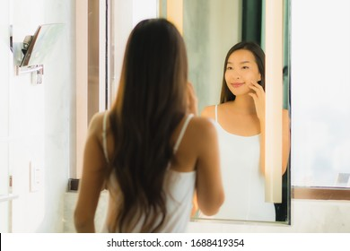 Portrait beautiful young asian woman check up her face and facial in bathroom interior