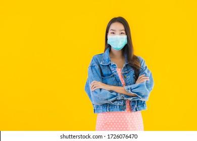 Portrait schöne junge asiatische Frau tragen Maske zum Schutz von Coronavirus oder Covid19 auf gelbem isoliertem Hintergrund