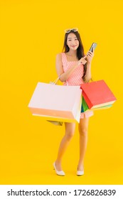 Portrait beautiful young asian woman with colorful shopping bag with smart mobile phone and credit card on yellow isolated background