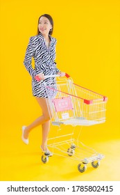 Portrait beautiful young asian woman with shopping cart for grocery shopping on yellow isolated background