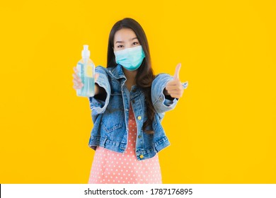 Portrait schöne junge Asianin trägt eine Maske zum Schutz von Coronavirus oder Covid19 mit Alkoholgel für sauberes, gelbem isoliertem Hintergrund