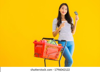 Portrait beautiful young asian woman shopping grocery cart from supermarket with credit card on yellow isolated background