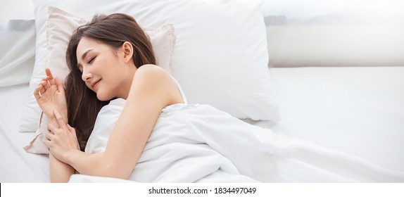 Porträt von schönen jungen asiatischen Lächeln genießen frische Bettwäsche und Matratze im Schlafzimmer modernen Wohnung. Teenage asia Girl ruhen, gutes Nachtschlafkonzept Panoramabanner