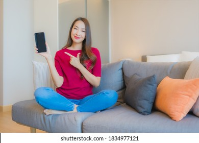 Portrait beautiful young asian woman use smart mobile phone on sofa in living area at bedroom interior