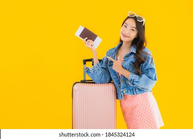 Portrait beautiful young asian woman with luggage travel bag with passport and boarding pass ticket on yellow isolated background