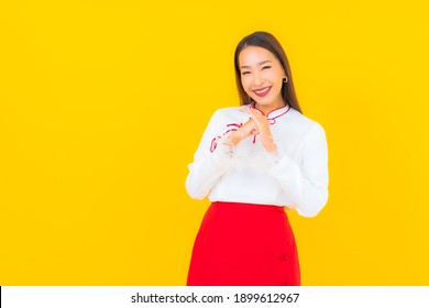 Portrait beautiful young asian woman smile in action on yellow background
