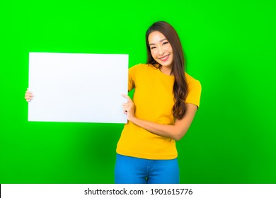 Portrait beautiful young asian woman show white empty billboard on green color background