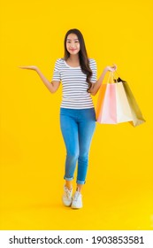 Portrait beautiful young asian woman with colorful shopping bag on yellow isolated background