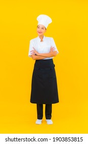 Portrait beautiful young asian woman in chef or cook uniform with hat on yellow isolated background