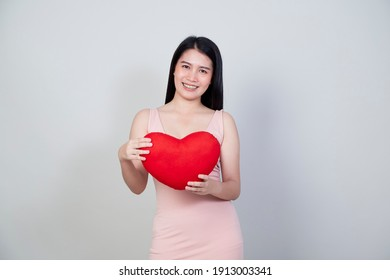 Portrait beautiful young Asian woman in dress show heart shape pillow isolated on light gray background with copy space