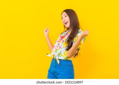 Portrait schöne junge Asiatin-Frau trägt buntes Hemd auf gelbem Hintergrund für das sonkran-Festival in Thailand