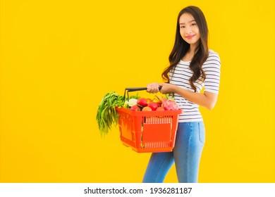 Portrait schöne junge Asiatin mit Körbchen-Warenkorb aus dem Supermarkt in einem Einkaufszentrum auf gelbem, isoliertem Hintergrund