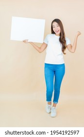 Portrait beautiful young asian woman show empty white billboard card paper on cream background