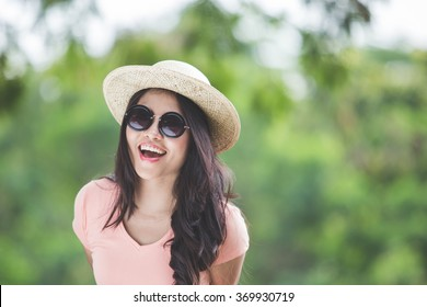 A portrait of a beautiful young asian woman wearing round hat on a park
