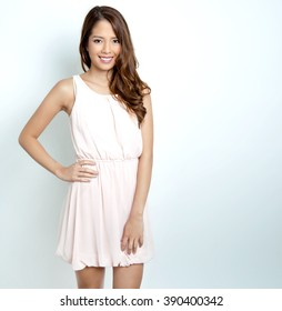 portrait of beautiful young asian woman with flawless skin and perfect make-up wearing pink spring dress