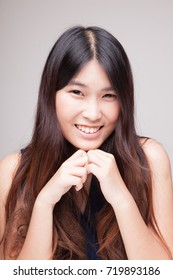 Portrait of beautiful young Asian woman on gray background