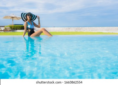 Portrait beautiful young asian women happy smile relax around swimming pool neary sea beach ocean in hotel resort