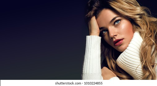 Portrait of a beautiful young attractive girl in a white sweater with blue eyes and long blond hair
