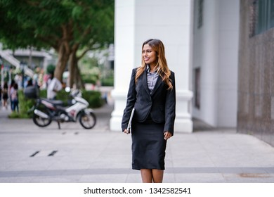 Portrait of a beautiful, young and attractive Singaporean Malay Asian woman in a business suit walking in a city in Asia during the day with her laptop computer. She is smiling confidently.