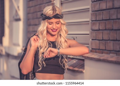 Portrait of a beautiful young attractive woman while walking on the street and checking the time on her watch. Street fashion livestyle concept