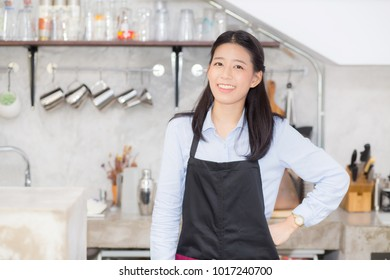 Portrait of beautiful young barista, asian woman is a employee standing in counter coffee shop, service concept.