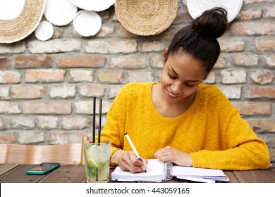 Portrait of beautiful young black woman sitting at cafe and writing notes