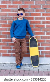 Portrait of a beautiful young blond boy in sunglasses near a shopping center outdoors. Handsome young boy in sunglasses with skateboard against a brick wall background