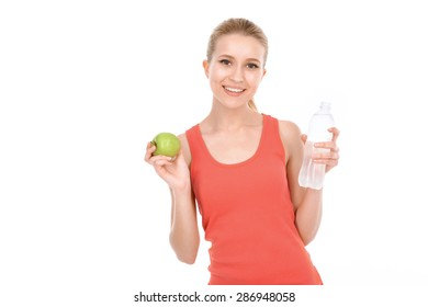 Portrait of a beautiful young blond fit girl wearing a red top holding an apple and a bottle of still water and smiling happily, isolated on a white background, waist up