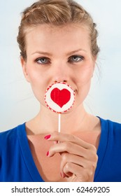 Portrait beautiful young blond girl with lollipop heart in her hand