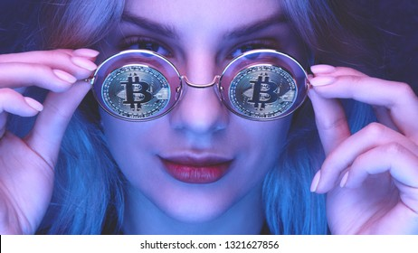 Portrait of a beautiful young blond woman with red lips in glasses with bitcoins close-up. Cryptocurrency concept. Creative neon lighting