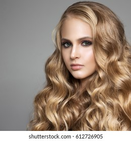 Portrait Of A Beautiful Young Blond Woman With Long Wavy Hair