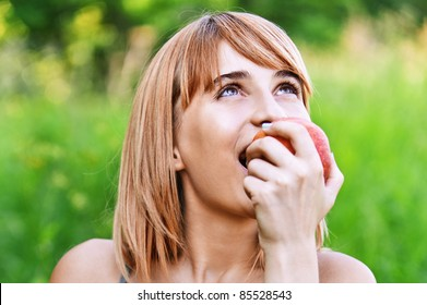 portrait of beautiful young blond woman eating fresh red apple at park