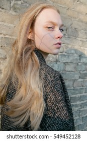 portrait of a beautiful young blonde in the autumn sun outing, against the background of a solar wall, model test