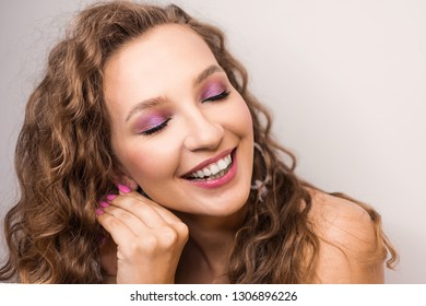 portrait beautiful young blonde curly girl posing in the studio with professional make-up and open  tooth smile pink mood