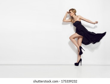 Portrait of beautiful young blonde girl in black dress. Fashion photo