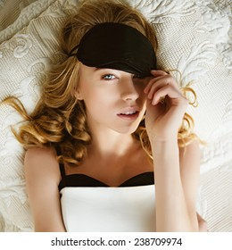 Portrait of a beautiful young blonde girl lying on a bed wearing a mask to sleep