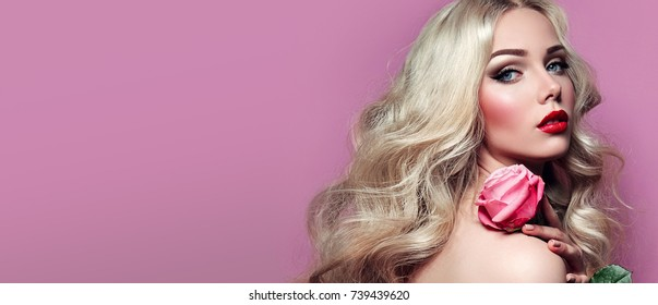 Portrait of a beautiful young blonde girl with a pink rose in hands on a pink background.fashion, beauty, makeup, accessories, make-up artist, boutique, beauty salon.fashion, beauty, makeup.