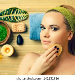Portrait of a beautiful young blonde touching her face with a special sponge at a spa salon. Perfect young skin. Skincare and haircare. Close up. Indoor shot