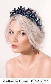 Portrait of beautiful young blonde woman with makeup and by a beautiful hair-do by the decorated stylish bijouterie
