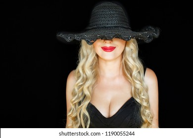 Portrait. Beautiful young blonde woman in black hat with a  decollete on dark background smiling mysteriously. Close-up.Bright red lips.