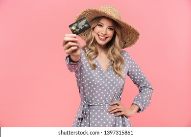Portrait of a beautiful young blonde woman wearing summer straw hat standing isolated over pink background, showing plastic credit card