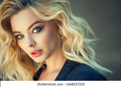 Portrait of beautiful young blonde woman. Blonde curly long hair woman with beauty makeup.
