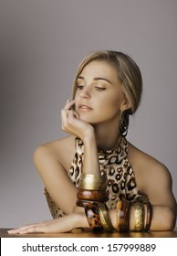 Portrait of beautiful young blonde woman resting her chin on her hand, with her long blonde hair tied back in a loose braid, wearing a leopard print top, tribal jewelry and sun kissed bronze makeup.