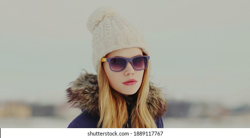 Portrait of beautiful young blonde woman wearing a hat outdoors